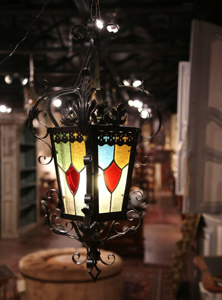 For a unique lighting feature, look no further than this beautiful, antique Gothic lantern from France, circa 1870. The French single light chandelier features four painted, stained glass panels including a small door to access the light bulbs; the