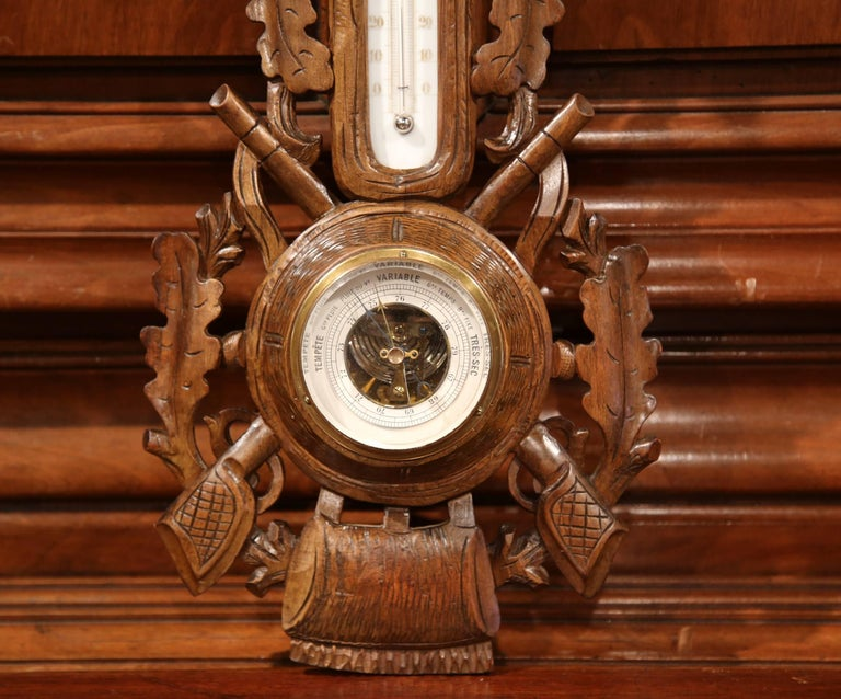 This elegant antique wall hanging barometer was crafted in France, circa 1880. The French decorative weather and temperature reading device is embellished with a traditional hunting theme. The Black Forest style piece features a carved deer at the