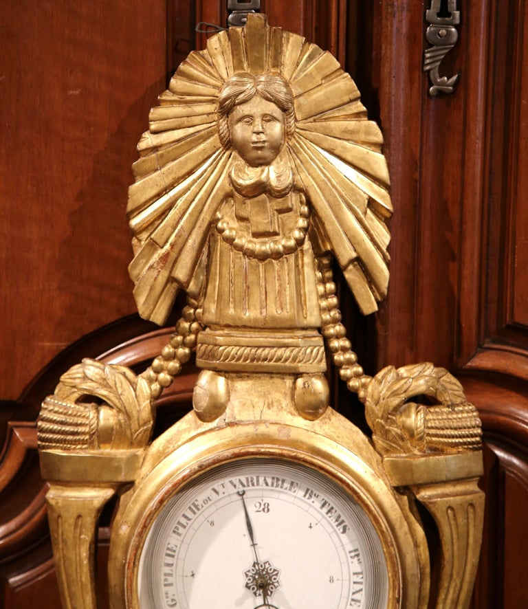 This beautiful, antique barometer was crafted in Lyon, France, circa 1760. The intricate wall hanging piece features a carved sun and angel on the pediment with decorative swags and ribbons on both sides. The impressive piece is in good condition