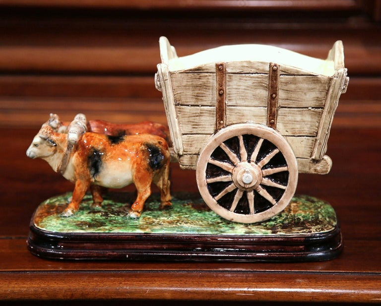 This colorful, antique Majolica sculpture composition depicts a Classic farm scene with cows pulling a cart. Created in France circa 1870, the ceramic jardinière features a pair of bovines joined together by a yoke, pulling a large wagon on wheel.