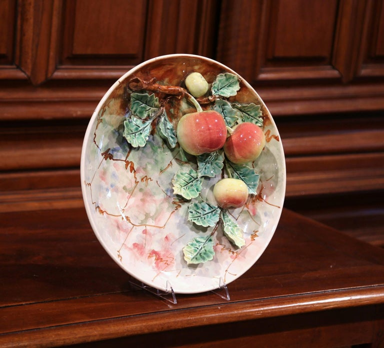 Hang this pair of large, colorful Majolica plates on your kitchen wall or display them on a shelf. Sculpted in France, circa 1870, one porcelain plate has four red and yellow apples hanging from a tree branch covered with green leaves. The other