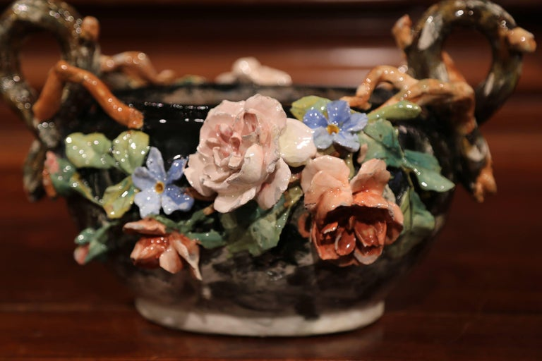 This elegant colorful hand painted majolica planter was sculpted in Montigny sur Loing, France, circa 1860. The ceramic jardinière with root shape handles features high relief soft pink, blue and beige rose flowers with pale green leaves, and brown