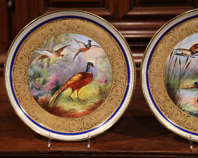 Beautiful pair of antique platters from France crafted, circa 1890, each colorful plate is hand-painted with gold leaf around the trim. The platters are signed on the front F. Chamel, they features swimming and flying ducks on one while the other