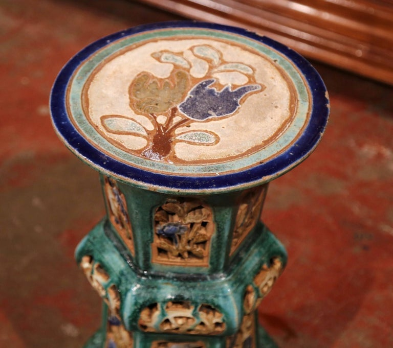 This interesting, porcelain garden seat was sculpted in France, circa 1920. In the green and brown palette, the round top has colorful painted flowers with intricate design on the base. This unique stool is in excellent condition and would make a