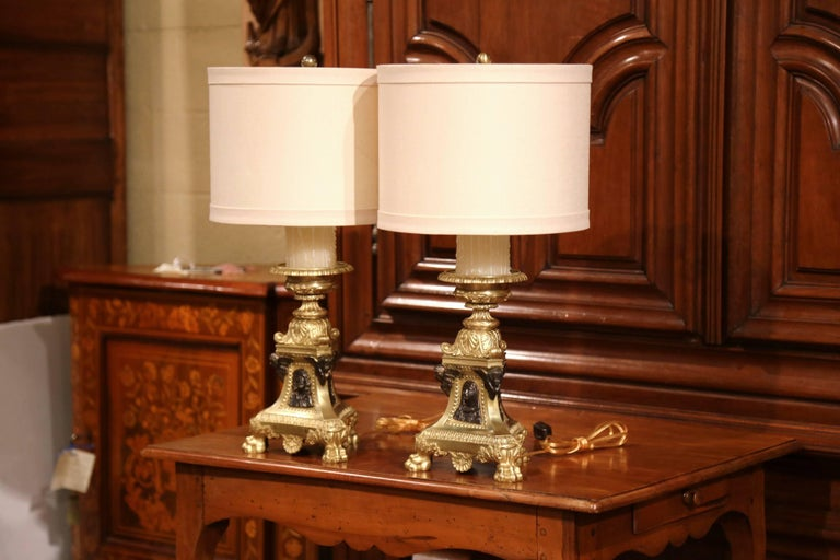 This elegant pair of antique church prickets were crafted in France, circa 1870. The ornate bronze candlesticks sit on a triangle base with three paw feet at the base; on all three sides, they feature a patinated center medallion representing the