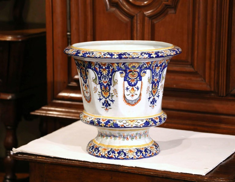 This elegant, large antique ceramic cache pot was crafted in Normandy, France, circa 1920. Signed on the bottom Rouen, the Classic, colorful planter features hand-painted decorative flowers in a blue, orange, white and yellow palette. The faience,
