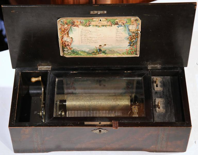 Beautiful antique music box from France, circa 1860. The wooden box with inlay band crank music box features eight different airs. The hinged lid opens to reveal a cylinder with a comb inside the lid on a lithograph board is a colorful scene of