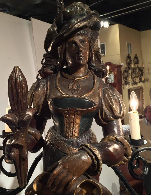 This interesting chandelier is a true statement piece for a wine cellar or bar area. Created in Germany, circa 1870, the standout chandelier has six arms and features a carved bust of a woman holding a shield in one hand and a torch in the other.