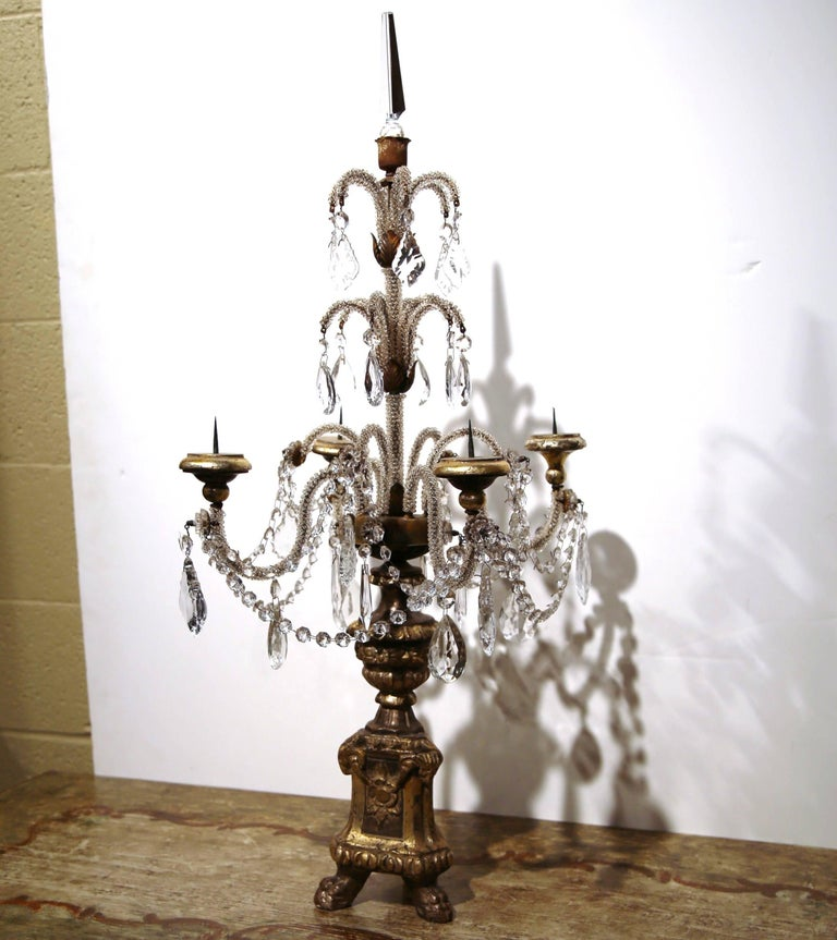 This delicate pair of candelabras was created in Italy, circa 1920. The elegant candle holders each have four arms with crystal and cut-glass pendants, gold leaf finish on the giltwood carved base with small feet, and a decorative glass finial to