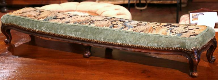This unique, antique foot stool, or prayer bench, will add color to any home. Created in France, circa 1870, the long fruitwood bench has six legs, curved feet, and a seat upholstered with a green velvet fabric and an 18th century Aubusson tapestry