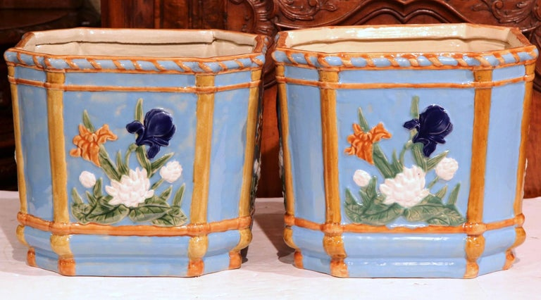 This fine antique Majolica jardinières were created in France, circa 1870. Octagonal in shape, both of the Classic, hand painted planters feature colorful flowers on all sides with a soft blue and orange palette background. These ceramic cachepots