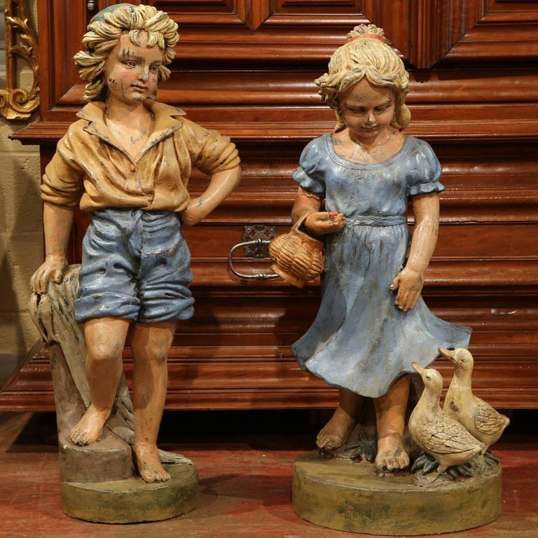 Add the charm of the French countryside to your home with this colorful pair of painted iron statues from Provence, France, circa 1970. The expressive figures depict a pair of children standing on round bases. The girl holds a basket with two ducks