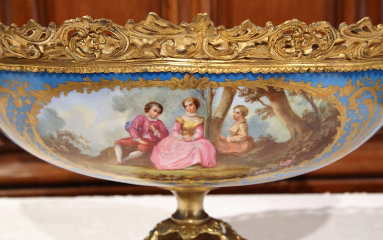 In the matter of Sevres, this elegant, antique jardinière was crafted in Paris, France, circa 1860. On one side, the oval planter features a delicate hand painted courting scene with a man and two women, and a floral vase decor on the opposite side.