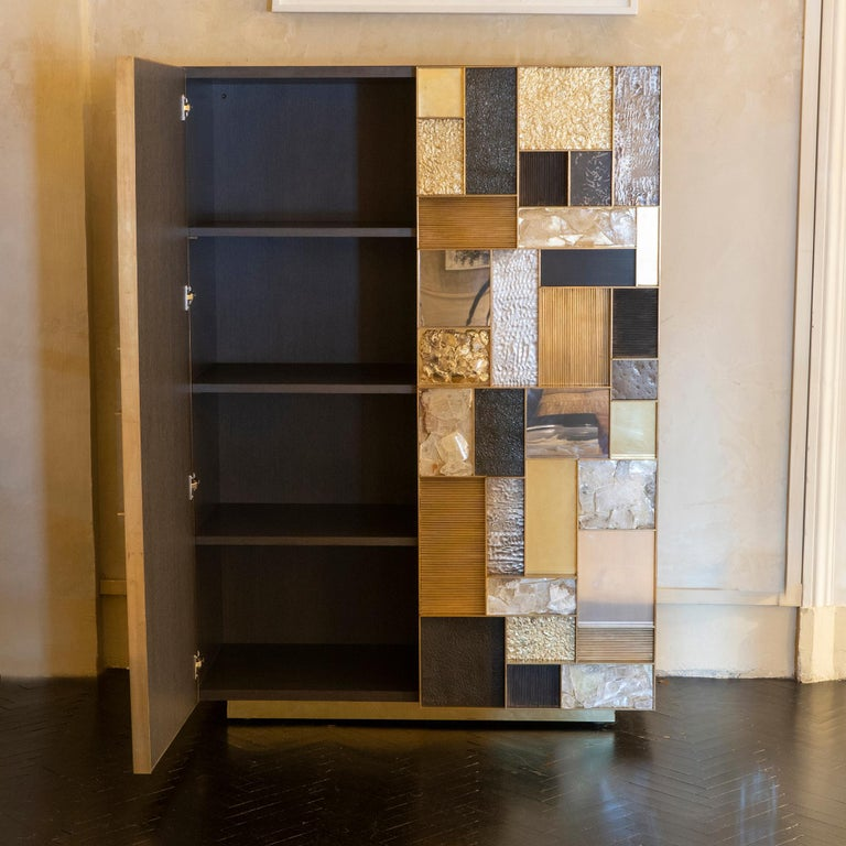Contemporary one of a kind cabinet part of the Flair Edition collection, structure covered in painted grey steel, sculptural doors with a geometric pattern and composition of brass wire, hammered brass, natural iron, hammered iron, gypsum crystal,