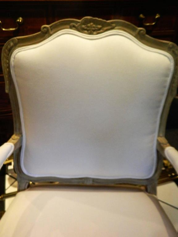 Louis XVI style upholstered open armchair, early 20th century. The upholstered back flanked by padded open arms centering an over upholstered seat, raised on cabriole legs.