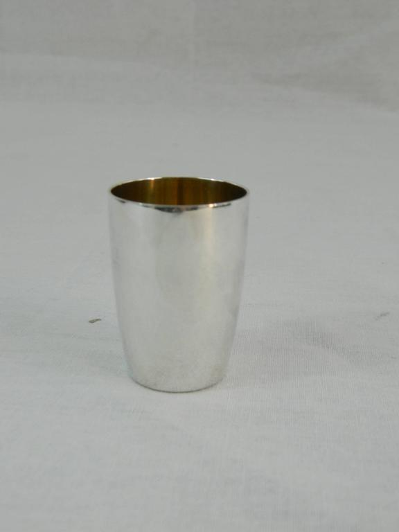 Set of four Tiffany & Co. sterling silver shot glasses, early 20th century. Gold interior.