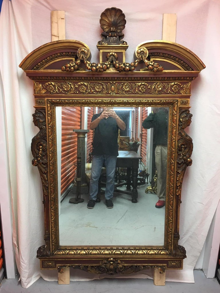Gold leaf wood carved mirror with figures on each side and a top shell, circa 1890.