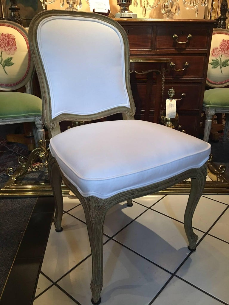 Set of four painted Louis XVI style dining chairs with cabriole legs, mid-20th century.