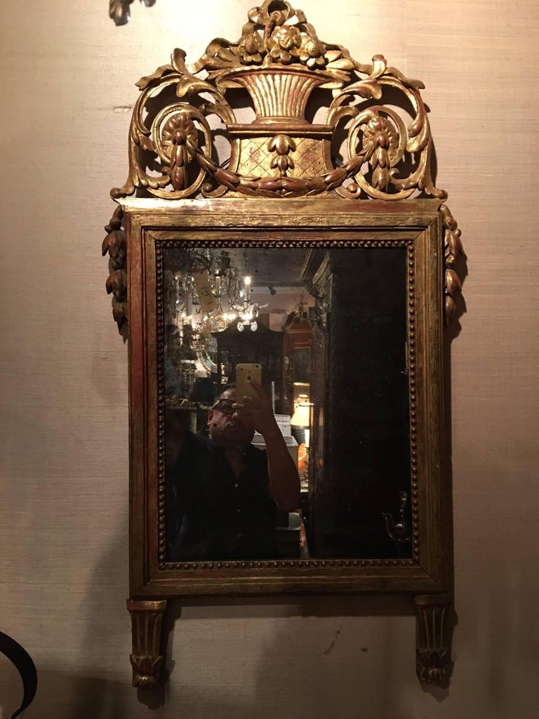 Italian Louis XVI style giltwood mirror, 19th century having bell flower swags and a rectangular mirror plate.