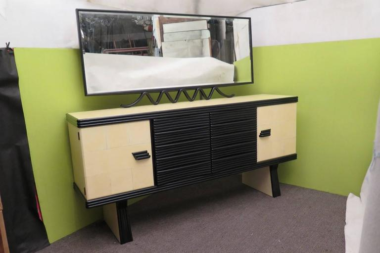 Sideboards completely polished in black shellac, with parchment leather inserts. Precisely the parchment leather is inserted on the two side doors, on the sides, and on the top. The central front black part has two doors above, and two drawers