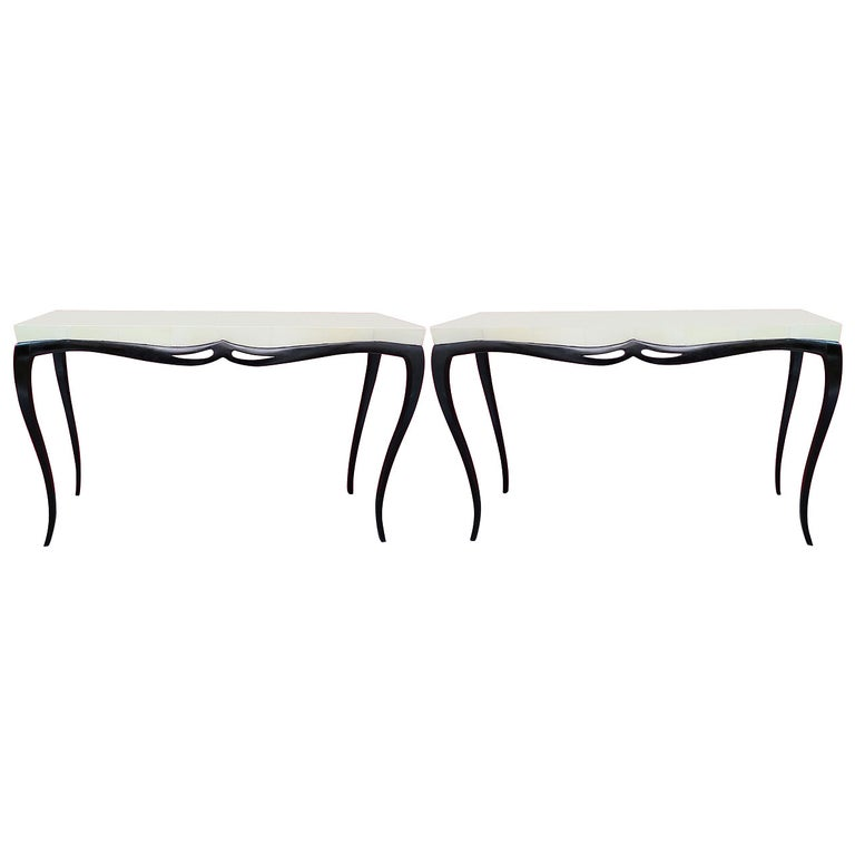 Rich in movements, pair of Art Deco console tables.   The wooden top is covered with parchment leather or goat skin and is rectangular with a sharp edge. The top rests on a frame in beech wood polished in black lacquer, moved to form a small acute