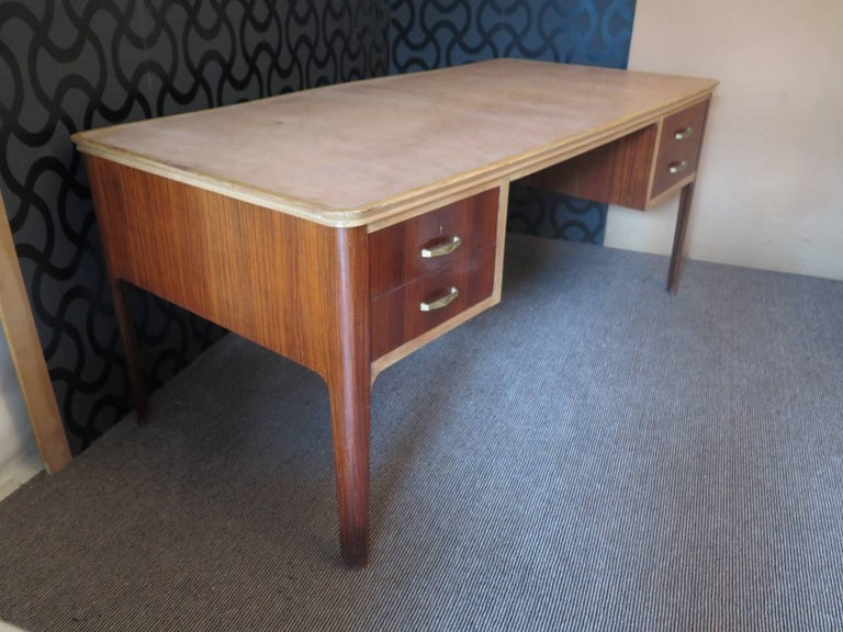 Italian desk from the middle of the century. Top of the desk all covered in light brown leather, with wooden edge running along the perimeter of the same, the corners are rounded. The part below of the top, that is the body of the desk, is all