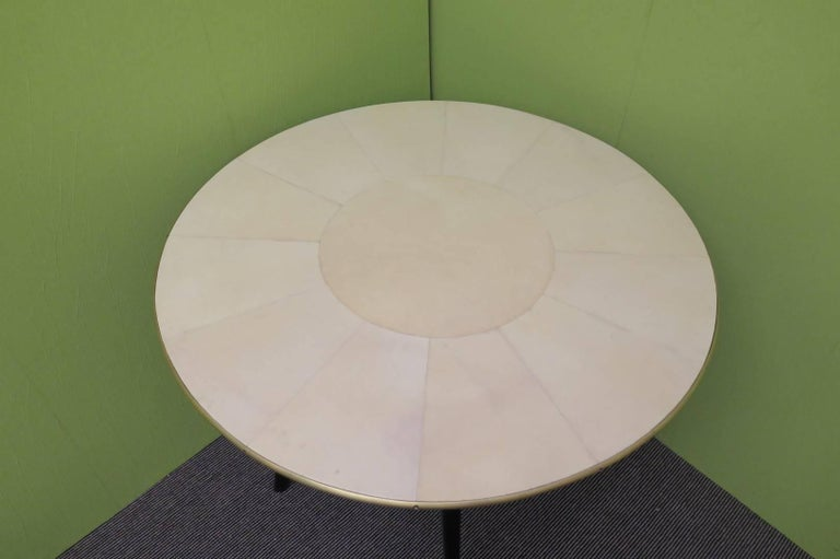 Art Deco gaming table, all covered in Parchment leather.  The card and tea table is composed of a top covered in parchment leather, an edged all around by a half-round brass rod. The half-round rod is fixed with brass screws sunk into it. The