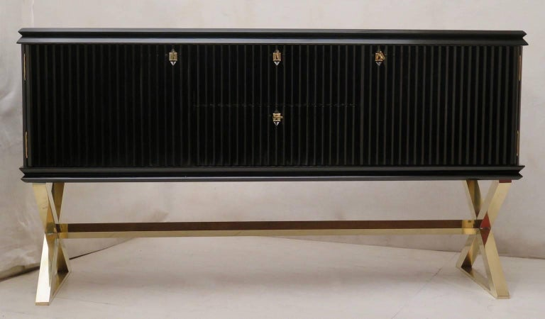 Elegant and refined sideboard in typical Italian style by Paolo Buffa, 1950. A perfect marriage between a black mirror polish and a finished brass.  All polished in black shellac, with polished brass leg. The body of the sideboard is composed of two