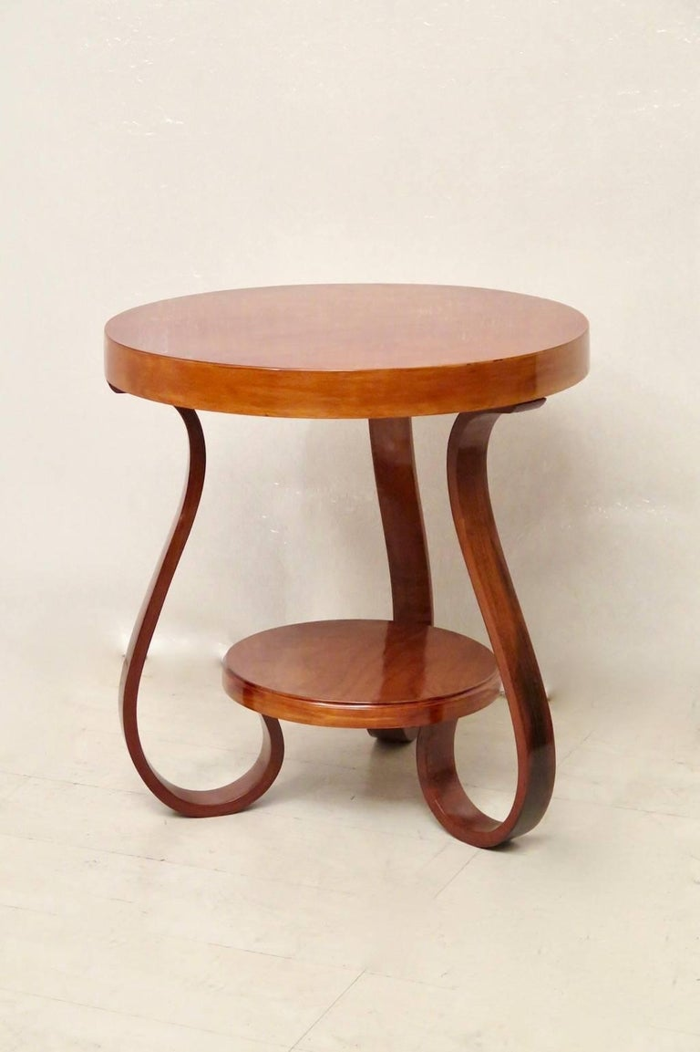 Very classic Art Deco curved wooden side table.  Of round shape and veneered cherrywood top, with a band that runs all around. Under the top, there are three legs bent by steam. These are held together by a cherrywood top, placed underneath. The