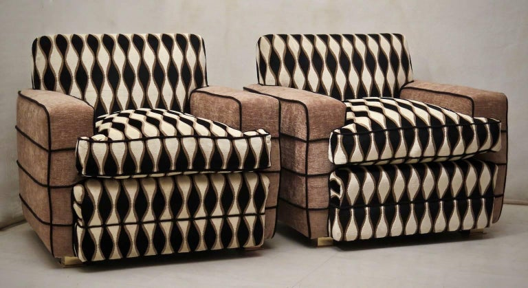 A pair of beautiful 1950s armchairs, all in fabric. Two types of velvet, one brown and the other white and black with geometric design. Black rope finishing. Very particular the geometric design of black, cream, and brown. To note the elegant brass