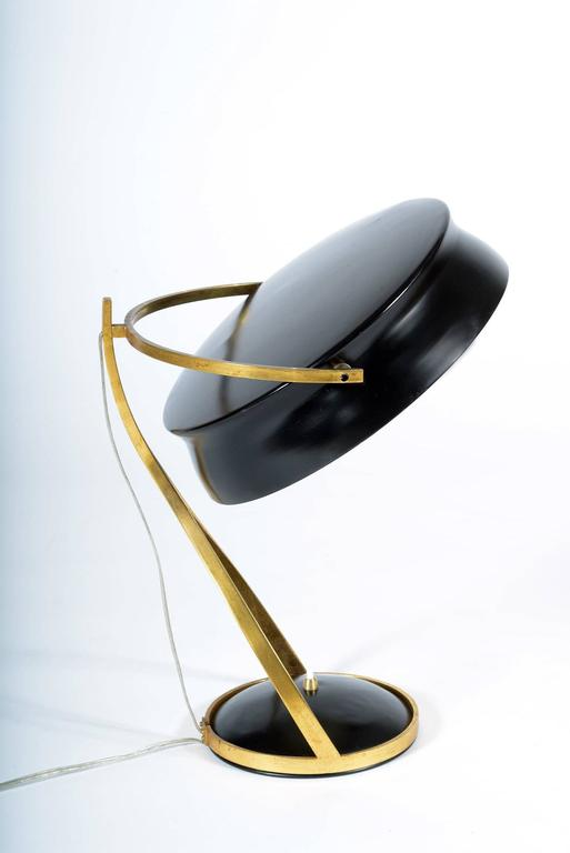 Brass and metal table lamps with adjustable black laquered shade. Interesting shaped structure where inside the shades move, base with the switch. Two bulbs in to the shade. The lamp is published in an advertisement of Chiarini Milan factory to