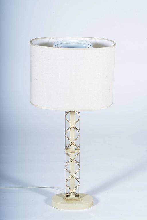 White laquered oval metal structures, oval thick and curved double crystal steak deeply beveled with gold lozenghe that keep on the decoration on the metal.
