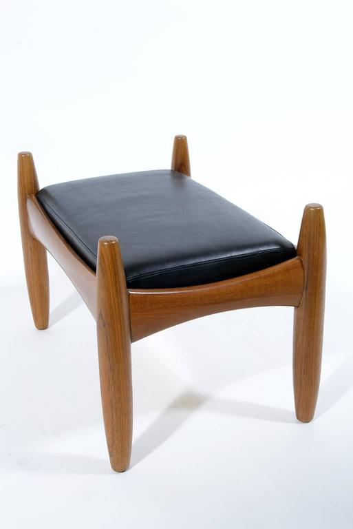 Soli sculptured teak wood and black leather upholster.