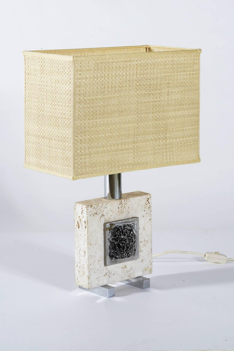 Italian 1970s pair of lamps, a piece of travertine support two chrome metal bass relief applied on each side.
