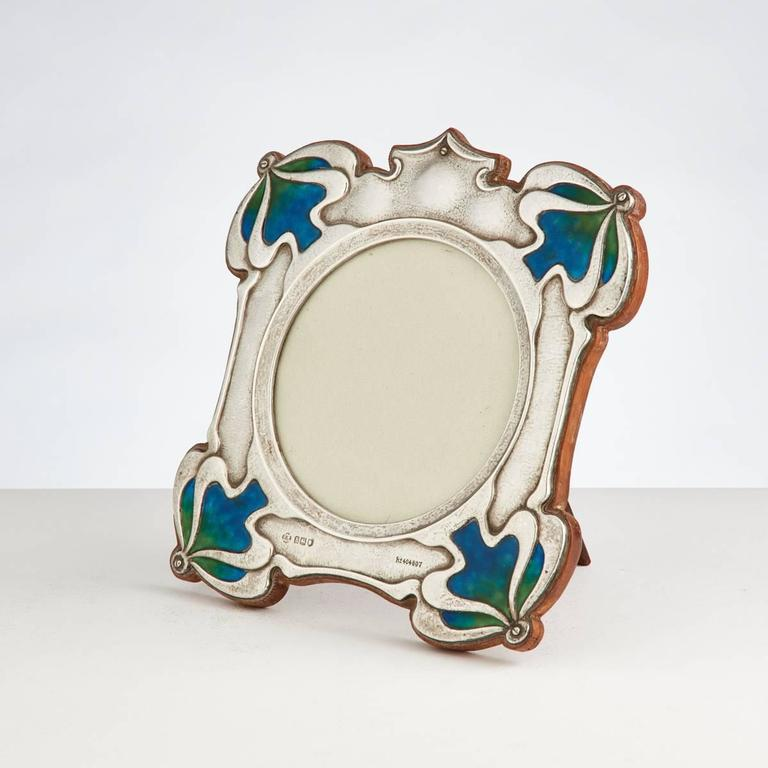 A beautiful quality Art Nouveau silver and enamel photograph frame by William Hutton with registration marks and dated London, 1906. The vibrant enamel is in perfect condition and it retains its original shaped oak back. The circular opening is 4
