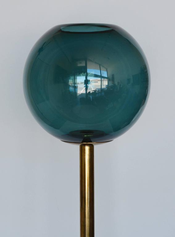Brass candleholder with a glass globe by Hans Agne Jakobsson. There is a small chip on the rim of the glass and a slight bend in the brass where the globe rests.