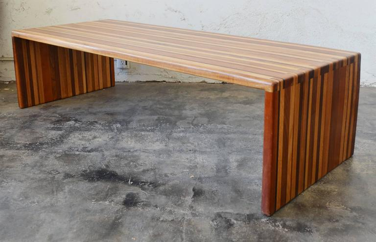 Studio made laminated mixed woods table or bench. This table is made up of at least five different varieties of hardwood. The ends are joined with dovetails. There is a deeper scratch on one side along the top.