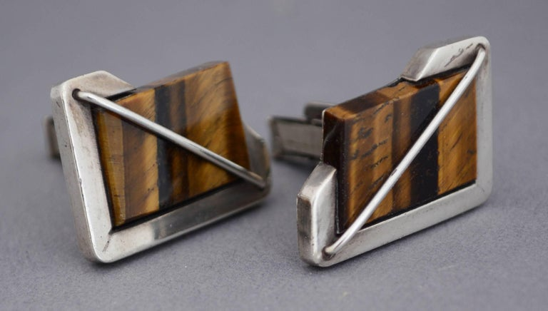 Sterling and tiger eye cufflinks with an asymmetrical modernist design. These were made by the Rancho Alegre shop in Taxco, Mexico.