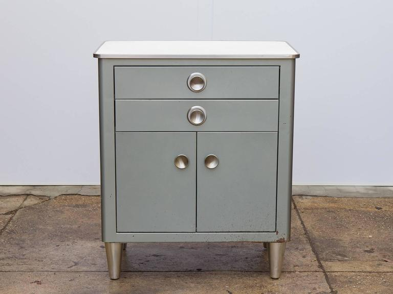 Small Modern Industrial display cabinet manufactured by American Metal Furniture, Inc. This hefty—yet sleek—Norman Bel Geddes-inspired steel cabinet sports round disc pulls on the drawers and cabinet doors. Charming linoleum speckled ivory