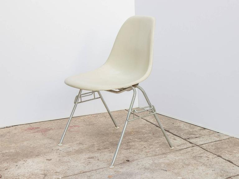 Original 1960s molded fiberglass parchment white shell chairs on stacking base, designed by Charles and Ray Eames for Herman Miller. Gleaming shells are in original condition, each with a distinct thready texture.  Shown here mounted on stacking