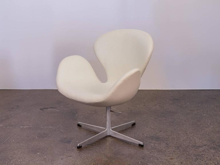 The iconic Swan chair designed by Arne Jacobsen in 1958. Attractive, ergonomic curves designed to sheathe it's sitter and follow resting limbs. Acquired from the original owner who purchased in the early 1960s. Meticulously upholstered in a creamy