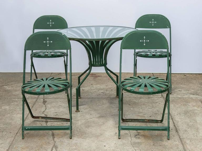Four cut-out wrought iron folding chairs and glass table in green enamel.  This - Francois Carre Style Garden Set At 1stdibs
