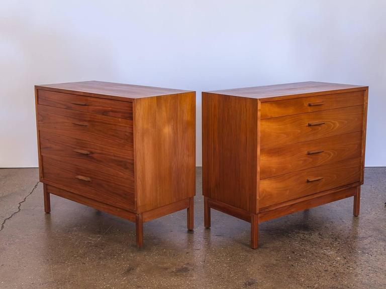 Pair of matching Mid-Century Modern walnut dressers with four drawers each. 1960s, in excellent vintage condition. Clean, simple lines reminiscent of George Nelson. Gorgeous walnut wood selection is gleaming and freshly polished. Each dresser is