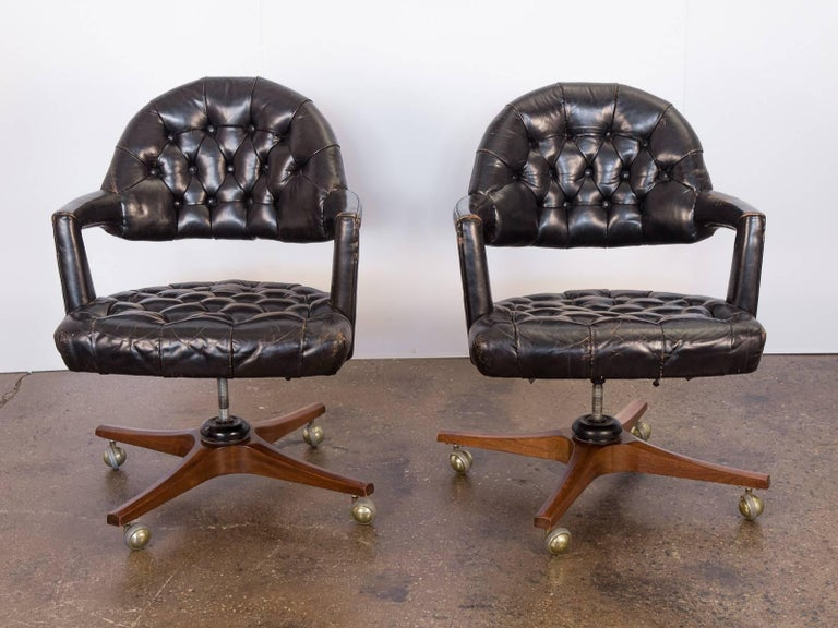 1950s open-back, tufted leather swivel chairs by Edward Wormley for Dunbar. These stylishly worn desk chairs feature an open-back form with angular, padded armrests. The tufted black leather is supple and sumptuous with a gorgeous patina. Adjustable