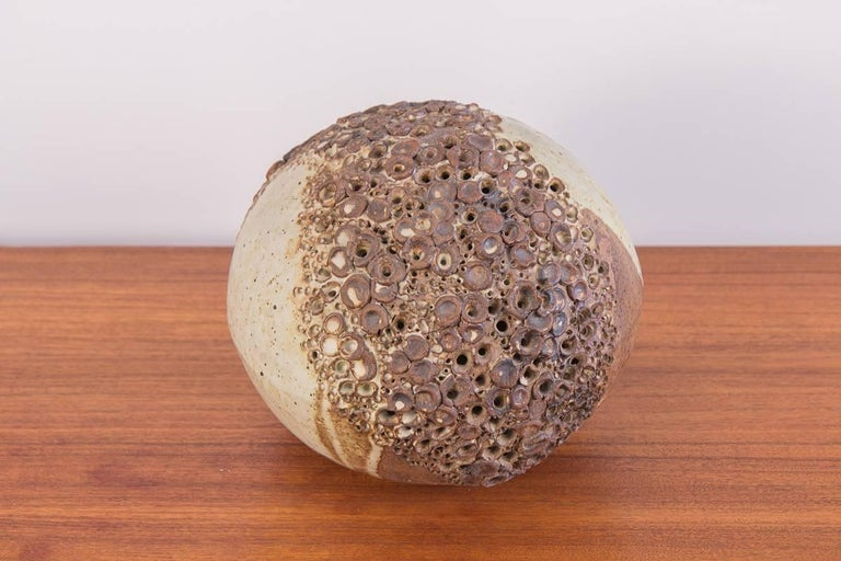 Hand-built earthenware sphere sculpture. Beautiful, rounded ceramic form adorns a band of perforations, evoking textures from the natural world. Glaze layering has variegated densities resulting in a beautiful, irregular matte finish. In excellent