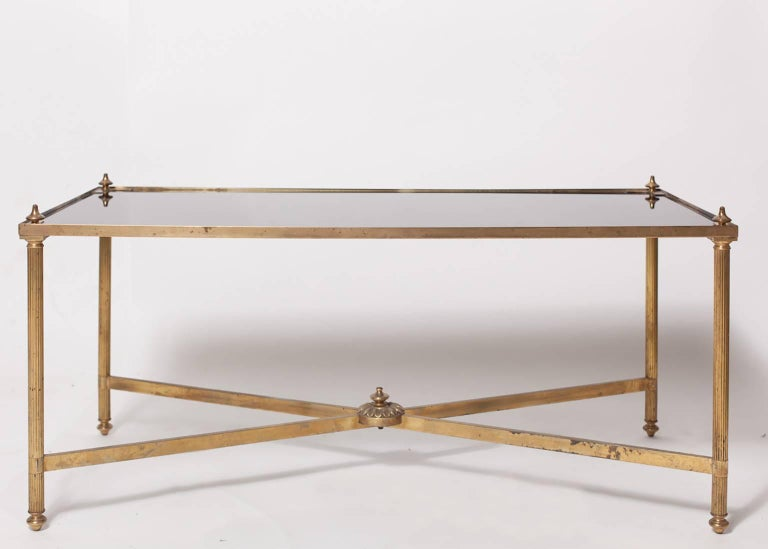 French Maison Jansen neoclassical style brass coffee or cocktail table with black glass top; the rectangular glass top fitted within corner spandrels; raised on reeded supports all joined by an x-form stretcher.