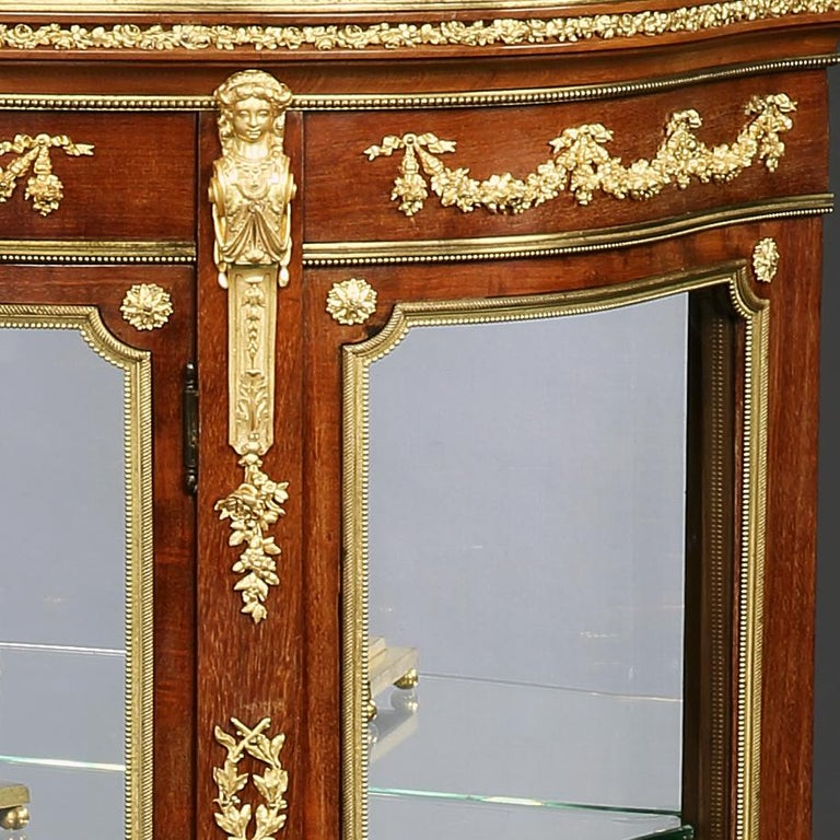 A French ormolu-mounted mahogany vitrine firmly attributed to François Linke, Paris.  Of demilune outline, constructed in mahogany, with gilt bronze mounts, in the Louis XVI Transitional style, rising from scroll and acanthus cast sabots, with
