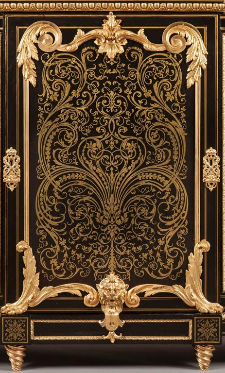 Constructed primarily in ebony and bronze, with cut-brass inlays; rising from tapering spiral toupie feet, the three lockable doors richly inlaid with brass arabesques, and having shaped gilt bronze mounts at the angles; the fields panel sides with