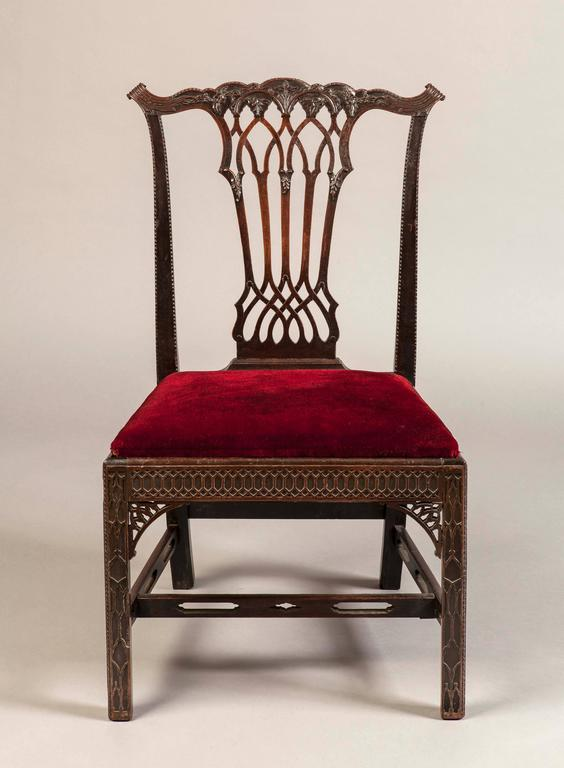 A Good Set of Eight Side Chairs in the Georgian Gothick Manner  Constructed in mahogany, which has been precisely carved; rising from square form blind fret carved chamfered legs and pierced stretchers; the fretwork seat rails house drop in