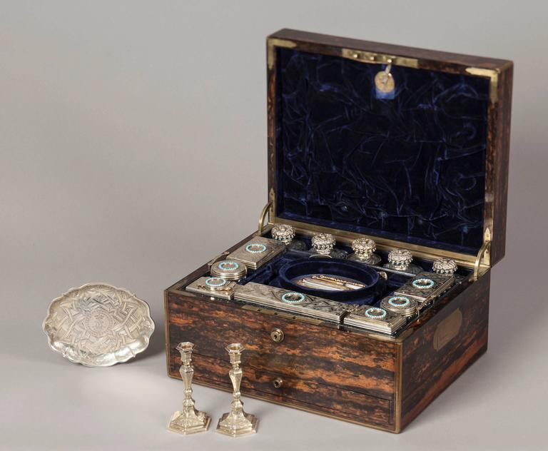 A mid-19th century lady's travelling dressing case.  The case is constructed in a finely marked coromandel, with inset brass handles and brass guard bands to the angles. The hinged lid rises to reveal in the upper section, a drop down document